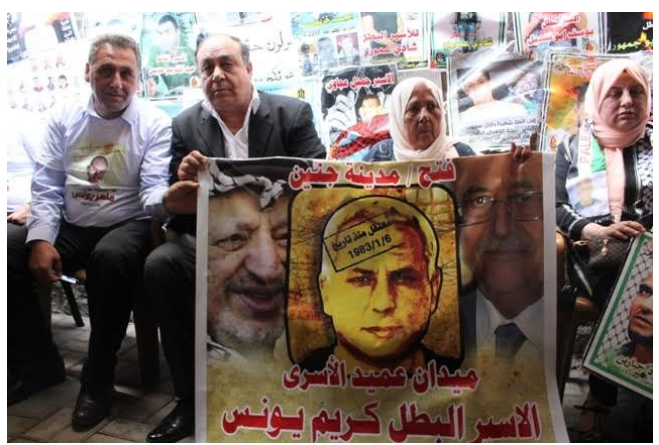 "Ibrahim Ramadan, governor of the Jenin district, next to the mother of terrorist Karim Yunes at the inauguration of the ""Karim Yunes square"" in Jenin . They hold a sign of Karim Yunes flanked on the left by Yasser Arafat and the right by Mahmoud Abbas. The Arabic reads, ""Fatah/Jenin. Detained since January 6, 1983. The square [named for] the oldest prisoner. Prisoners and hero, Karim Yunes"" (bukra.net, May 18, 2017)."