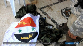 The flag of the Palestinian Al-Quds Brigade near a vest, found by ISIS (Akhbar Al-Muslimeen, January 17, 2018)