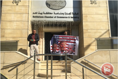 Palestinian activists at the entrance to the Palestinian bureau of commerce in Bethlehem after the visit of the American delegation. They hold signs denouncing the United States and Israel.