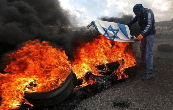 A masked Palestinian burns the Israeli flag during a riot in Judea and Samaria (Palinfo Twitter account, March 17, 2018).