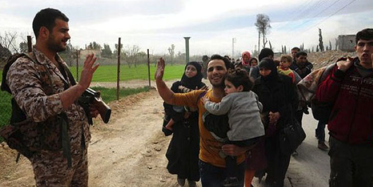 Syrian soldier waving goodbye at Syrian residents evacuated from eastern Al-Ghouta (SANA, March 24, 2018).