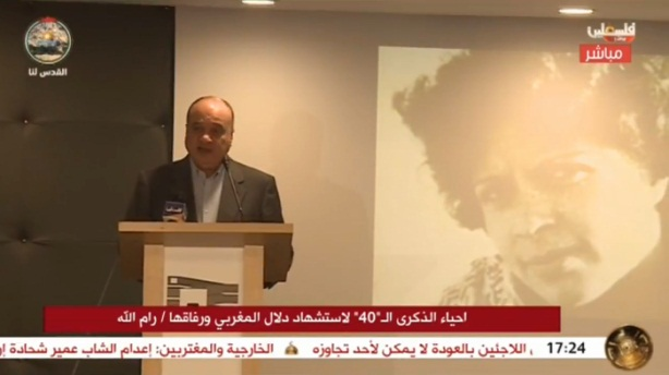 Nasser al-Qudwa gives a speech at the Yasser Arafat Institute in Ramallah with a picture of Dalal al-Mughrabi on a screen behind him.