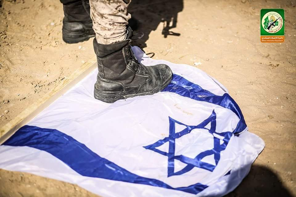 Stepping on an Israeli flag (PalInfo's Twitter account, March 25, 2018)