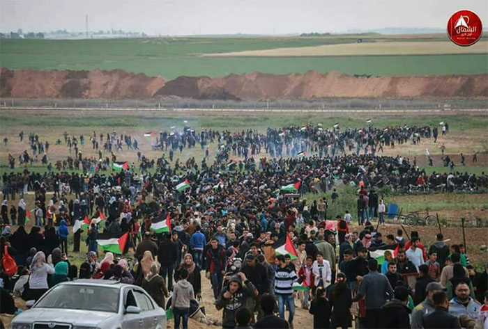 Palestinian demonstrators near the border security fence.
