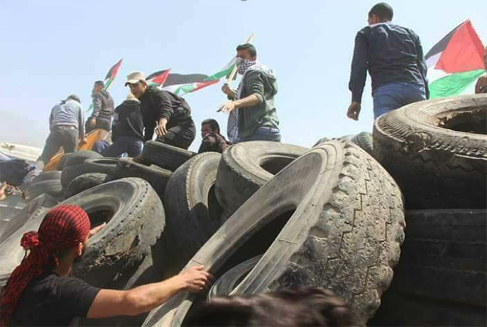 Palestinians collect tires in the eastern Gaza Strip for burning at the