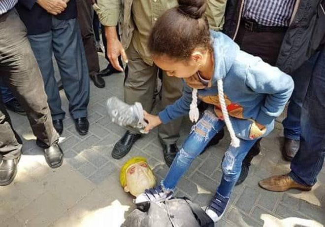 A girl stands on the neck of an effigy of Donald Trump and throws shoes at it during a demonstration in Nablus (Twitter account of QudsN, April 14, 2018).