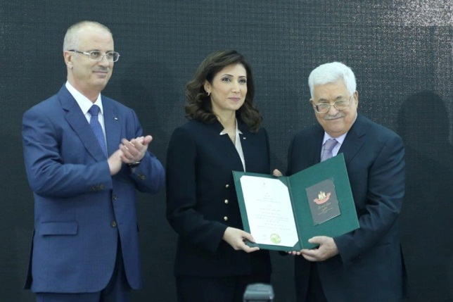 'Ala Awad receives an award for the activities of the bureau. At the left is Rami Hamdallah, prime minister of the national consensus government (Facebook page of Palestinian central bureau of statistics, March 29, 2018).