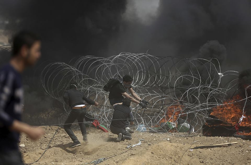 Attempts to vandalize the barbed wire fence parallel to the border fence in the Gaza Strip (Facebook page of Shehab, April 13, 2018).