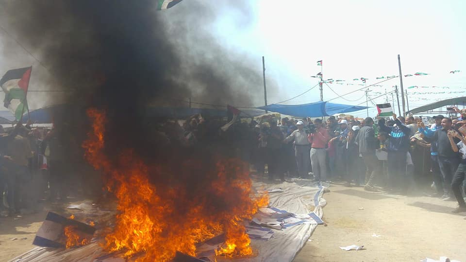 """Palestinians burn Israeli flags during the """"great return march"""" on April 13, 2018 (Facebook page of al-Risalah, April 13, 2018)."""