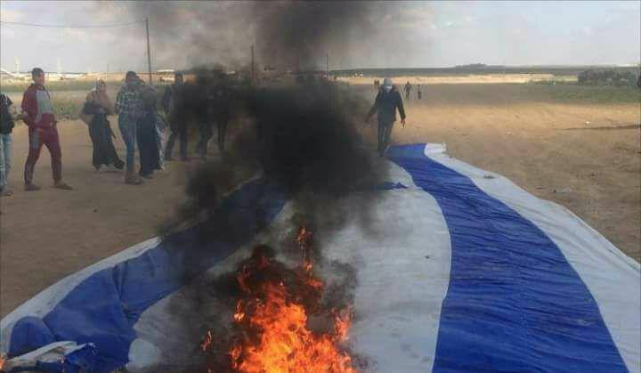 """Palestinians burn an Israeli flag during the """"great return march"""" (Facebook page of al-Risalah, April 13, 2018)."""