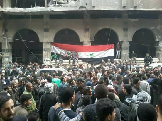 Syrian civilians celebrating in Duma, with the Syrian flag in the background (Butulat Al-Jaysh Al-Suri, April 12, 2018)