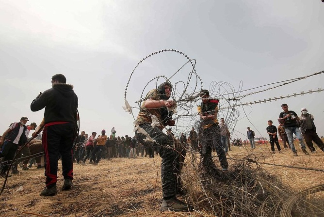 Palestinian rioters pulling and then cutting the barbed wire fence east of Khan Yunis (PALINFO, April 27, 2018).