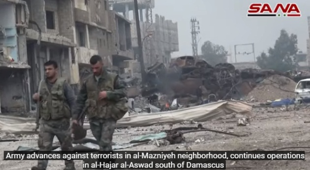 Syrian army soldiers in the Al-Madhaniya neighborhood. An embankment and a checkpoint set up by ISIS in the neighborhood are visible in the background (SANA, April 28, 2018)