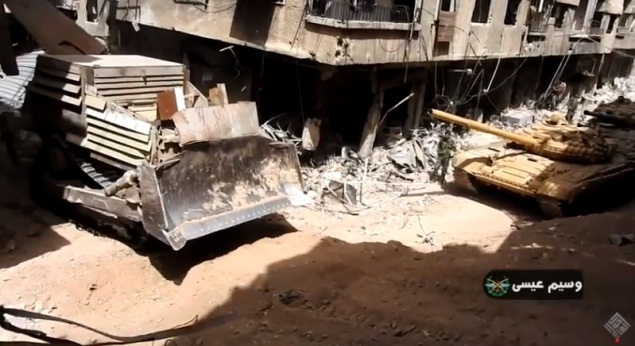 Bulldozer near Syrian army tanks in one of the streets in the Yarmouk refugee camp.