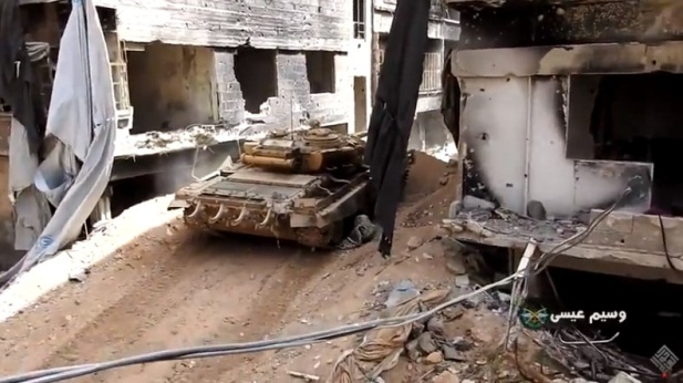 Syrian army tank in the Yarmouk refugee camp attacking ISIS targets after a bulldozer blazed a way for it to pass through an embankment (haol alaalam 24 YouTube Channel).