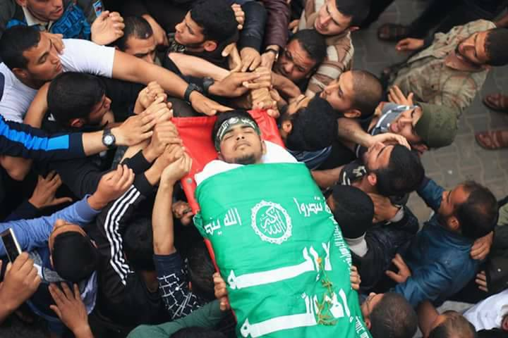 Photos of Bahaa Qudeih's funeral. His body is wrapped in a Hamas flag and operatives of the military wing are beside him (Facebook page of the Qudeih family, May 6, 2018)