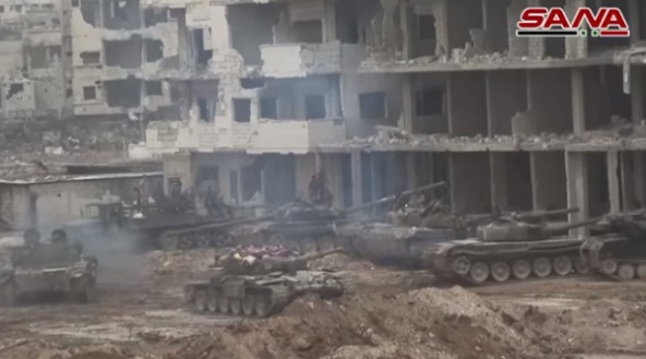 Syrian army tanks in a staging zone near damaged buildings in the Al-Hajar al-Aswad neighborhood.