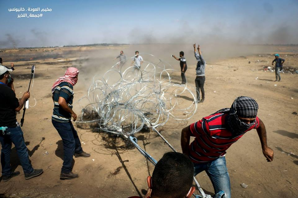 Palestinian rioters drag away the barbed wire near the security fence east of Khan Yunis.