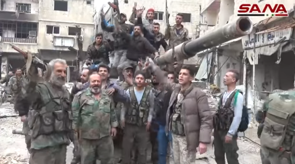 Syrian army soldiers and operatives of supporting militias cheering near a Syrian tank in the Al-Hajar al-Aswad neighborhood (SANA, May 10, 2018)