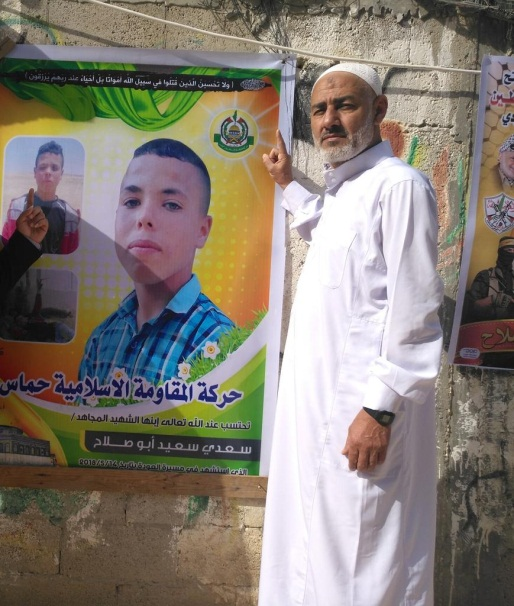 A picture the uncle posted to his Twitter account of himself standing next to a poster issued by Hamas commemorating Saadi Abu Salah (Twitter account of Abu Fahmi Abu Salah, May 16, 2018)