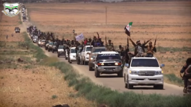Convoy of vehicles as part of the military show. Militiamen waving flags of the organization and the Free Syrian Army.