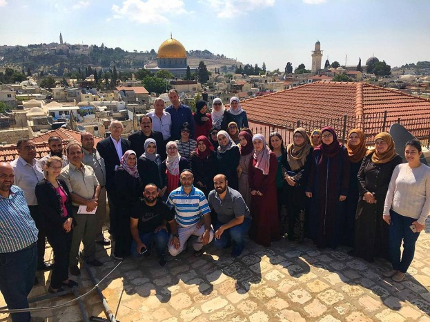 Sabri Saidam, PA minister of education (back row, fifth from left), during a visit to east Jerusalem, poses with employees of the Palestinian education administration in the [Palestinian] Jerusalem district, with the Temple Mount in the background (Facebook page of Sabri Saidam, May 30, 2018).