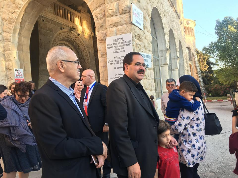 Sabri Saidam, PA minister of education, arrives at the graduation ceremony of the al-Asrar school. To his right is Samir Jibril, head of the education authority in the [Palestinian] Jerusalem district (Facebook page of the Augusta Victoria hospital, June 4, 2018).