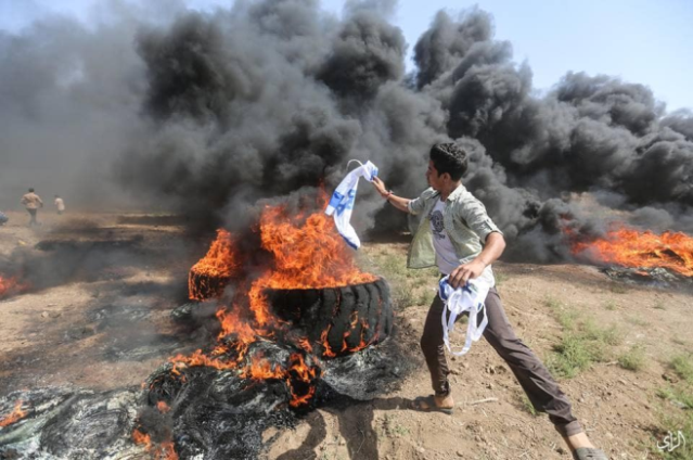 "Burning the Israeli flag (Facebook page of the ""supreme authority of the great return march,"" June 8, 2018)."