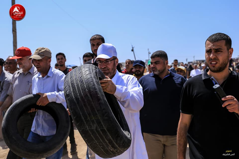 Senior Hamas figure Fathi Hamad carries a tire on his way to the