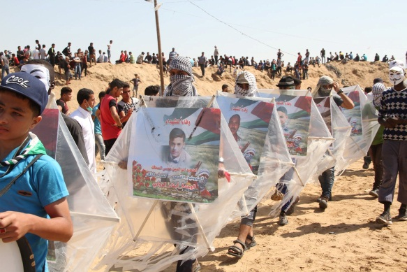 "Children carry kites with pictures of shaheeds (Facebook page of the ""supreme authority of the great return march,"" June 8, 2018)."
