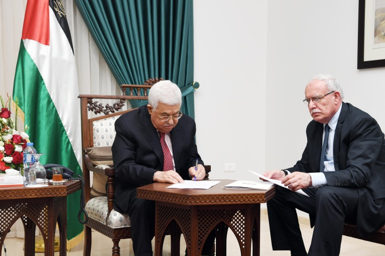 Mahmoud Abbas signs documents for joining seven more international conventions. At the right is Riyadh al-Maliki, PA foreign minister (Wafa, June 7, 2018).