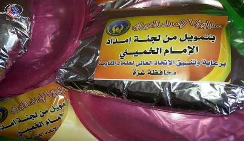 "Meals distributed for Ramadan. The sticker reads, ""The charity kitchen of the Imam Khomeini Support Committee; funded by the Imam Khomeini Support Committee; under the aegis of and coordination with the Global Association of Muslim Scholars of the Resistance; Gaza district (al-Alam TV, Iran, June 11, 2018)."