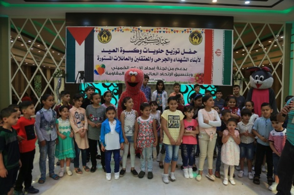 "Ceremony of distributing support to children. The sign reads, ""Ceremony of distributing candy and clothing for the holiday to children of the shaheeds, wounded and prisoners, and children of needy families; with the support of the Imam Khomeini Support Committee and in coordination the Association of Muslim Scholars of the Resistance (IRNA in Arabic, June 14, 2018)."
