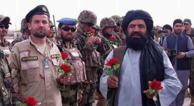 Taliban fighters and Afghan army soldiers holding flowers to mark the ceasefire agreement in advance of Eid al-Fitr.