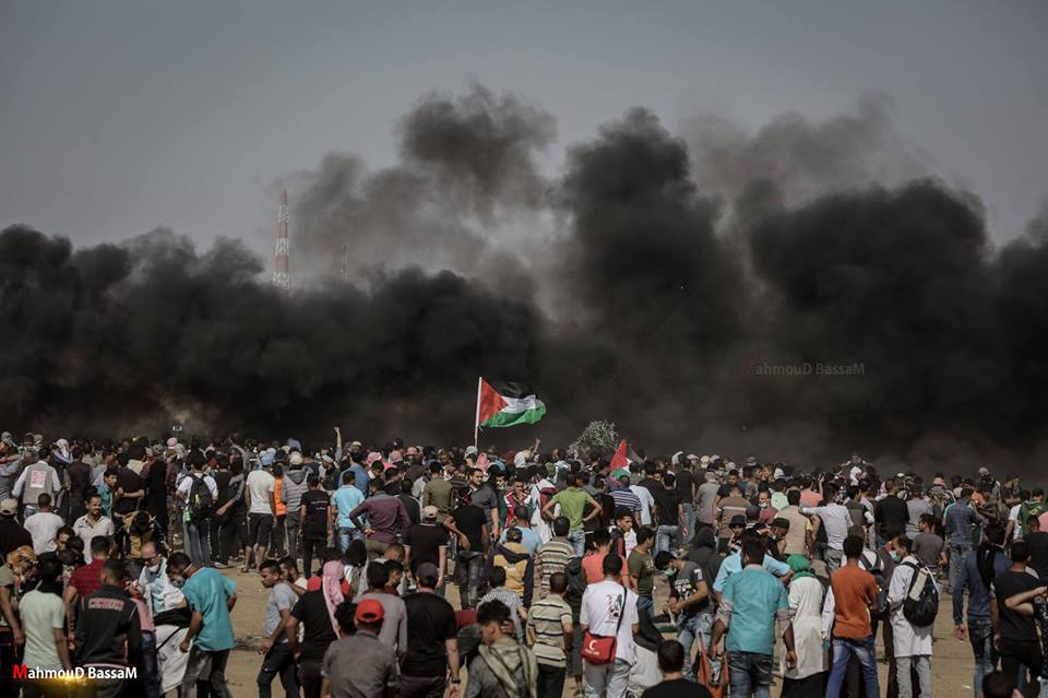 A crowd of Palestinians tries to break through the border fence into Israeli territory, hidden by smoke from burning tires (Shehab Facebook page, May 11, 2018).