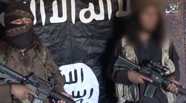 Two ISIS operatives next to the ISIS flag. The operative on the right (whose face has been blurred) is presenting the Iraqi government with an ultimatum (www.k1falh.ga, June 23, 2018).