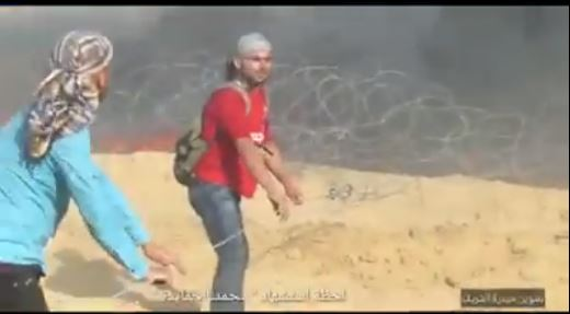 ‏‏Muhammad al-Hamayda (red shirt) sabotages the barbed wire near the security fence in eastern Rafah a few minutes before he was killed by IDF fire (Facebook page of Kheiri Abu Fires Abu Sinjar from Rafah, June 30, 2018)