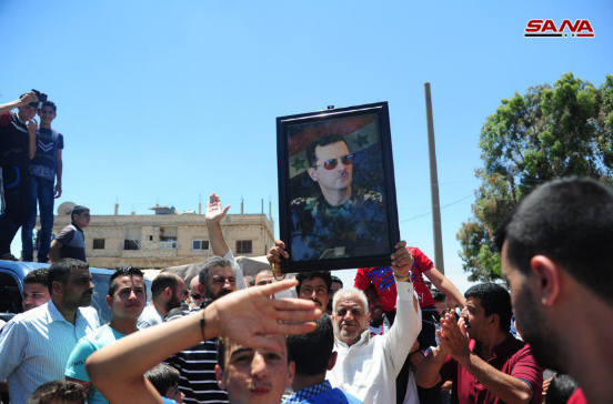 Residents of the town of Abta, north of Daraa, welcoming the arrival of the Syrian army and waving a picture of Syrian President Bashar Assad (SANA News Agency, June 29, 2018).