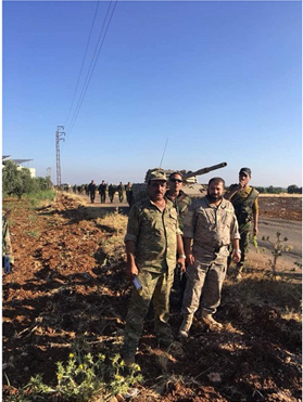 Abu Ajeeb (center) standing near a tank. Soldiers march in formation in the background. Their identities cannot be verified because militia fighters wear Syrian army uniforms.