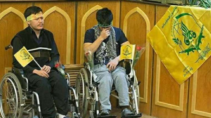 The Fatemiyoun Brigade flag displayed next to two wounded Fatemiyoun fighters at a ceremony held in Iran to honor the wounded (The information office of the Syrian revolutionary force, April 24, 2018). Hundreds of fighters wounded in the fighting in Syria were treated in Iranian hospitals.