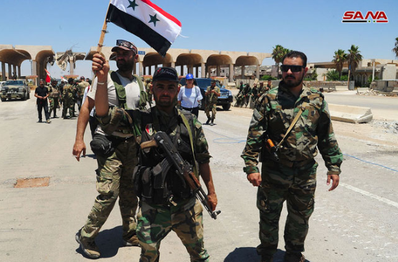 Syrian army soldiers at the Naseeb border crossing, waving photos of the Syrian president and Syrian flags (SANA, July 7, 2018)