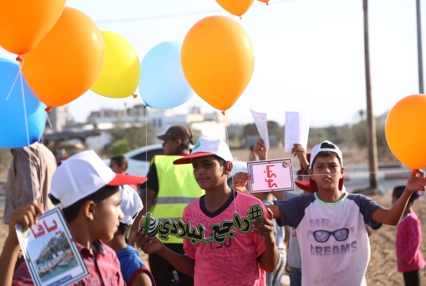 Launching balloons with the slogan of the summer camps and the names of cities and villages occupied by Israel in 1948. The boy at the left holds a notice with the word