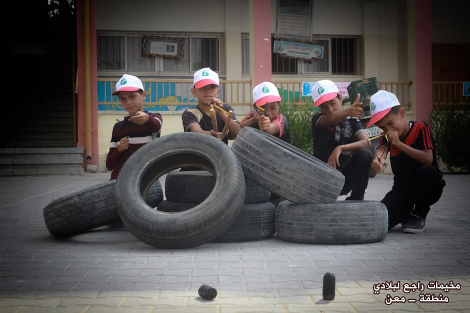 Using slingshots while hiding behind tires in the summer camp in the Ma'an region – Abu Obeida branch in Khan Yunis (Facebook page of the committee of the summer camps in the Ma'an region, July 15, 2018).