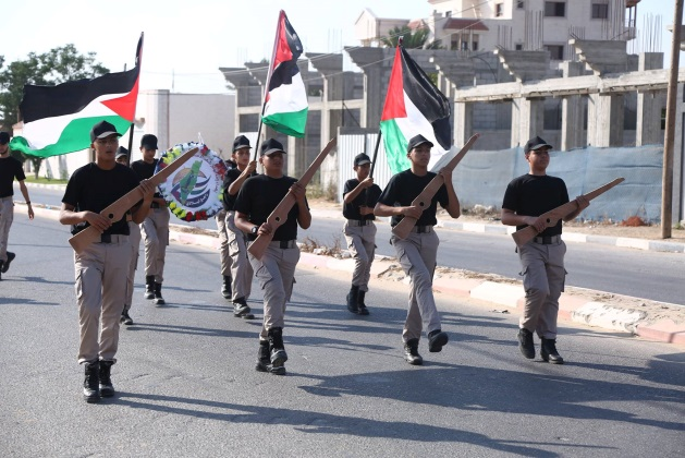 Gazan youths march with wooden rifles at the opening ceremony of the summer camps (Facebook page of the summer camps committee in Khan Yunis, July 14, 2018).