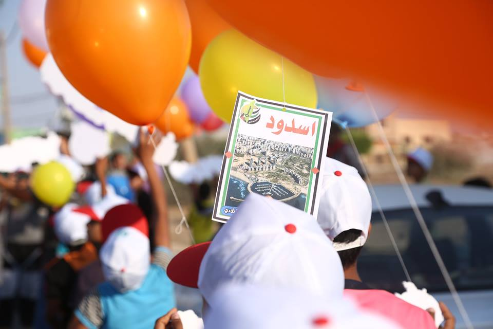Youths launch balloons at the opening ceremony. Slips of paper are attached to the balloons with the names of the camps and of the cities and villages the Palestinians fled from in 1948. Right: A ballon with