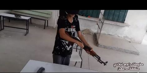 ‏‏A lesson in disassembling and reassembling a rifle. The lesson took place in one of the classrooms in a local school (Facebook page of the summer camps committee in the Ma'an area, July 14 and 15, 2018).