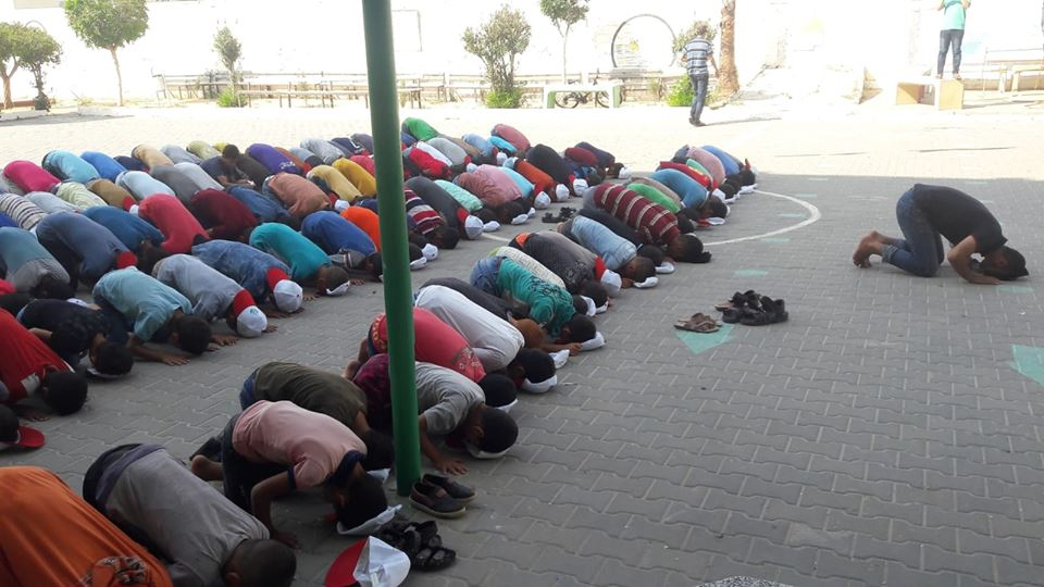 Mass prayers held in the summer camp in the town of Khirbat Ikhza'a, east of Khan Yunis (Facebook page of the summer camps committee in Khan Yunis, July 17, 2018).