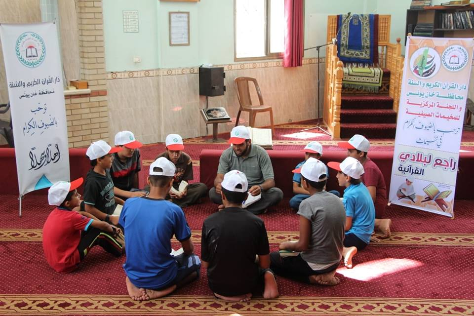 Qur'an memorization at a summer camp in the Khan Yunis refugee camp in cooperation with the Dar al-Qur'an wal-Sunna association (Facebook page of the summer camps committee in Khan Yunis, July 16, 2018).