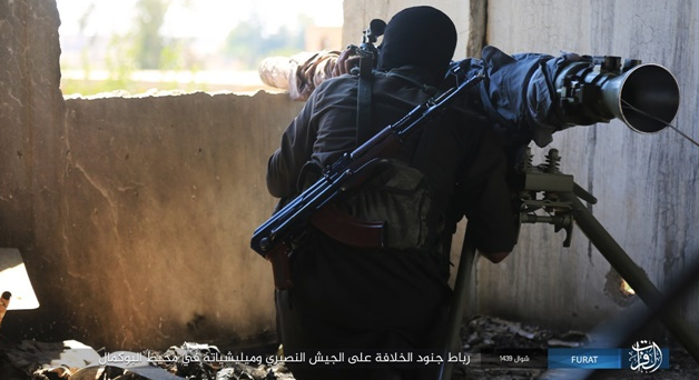 ISIS operatives pointing a gun at Syrian army positions in the Albukamal area.