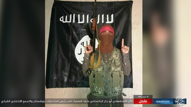 ISIS suicide bomber before leaving to carry out the attack, with ISIS flag in the background (ISIS-affiliated website www.k1falh.ga, July 13, 2018)